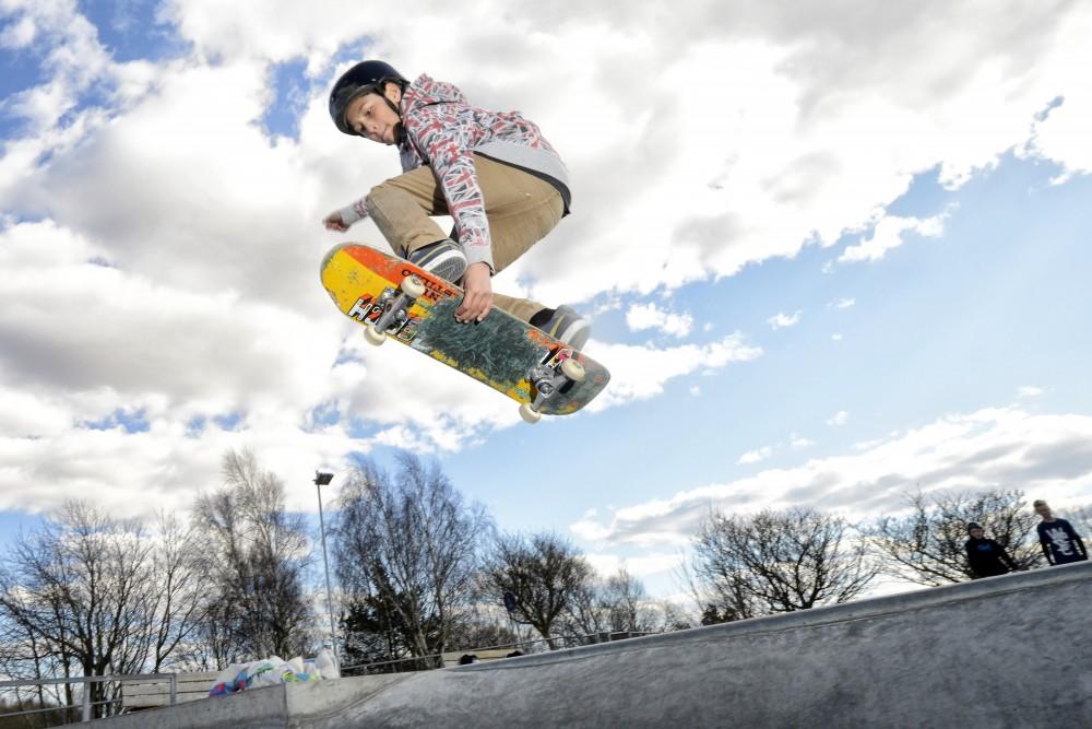 Kille på skateboard mitt i ett hopp