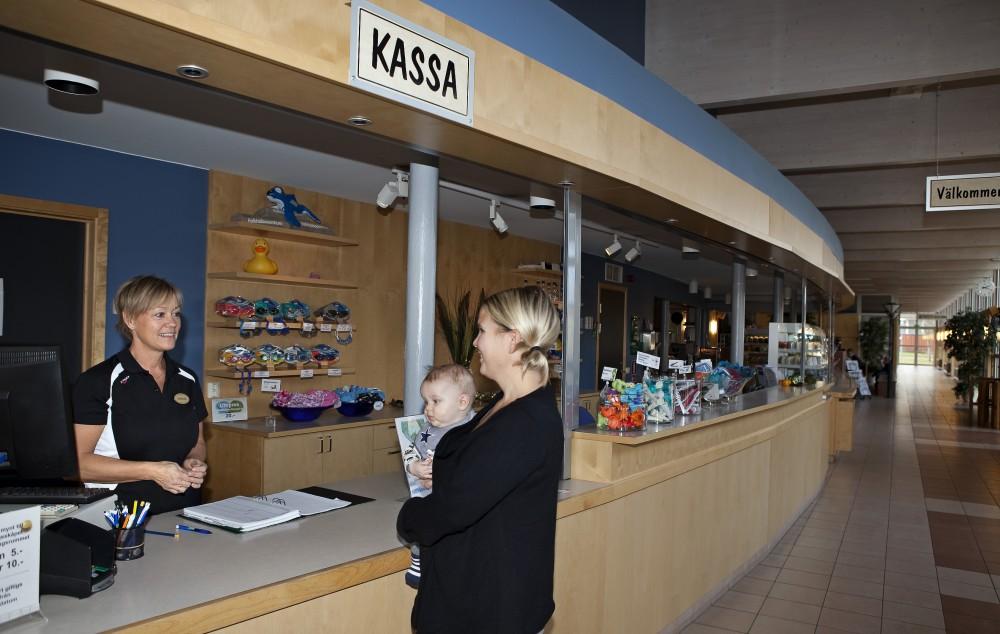 Kvinna med barn pratar med personal vid kassan