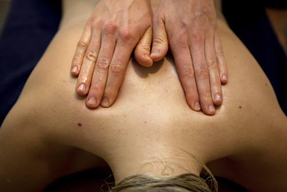 Händer som masserar skuldror