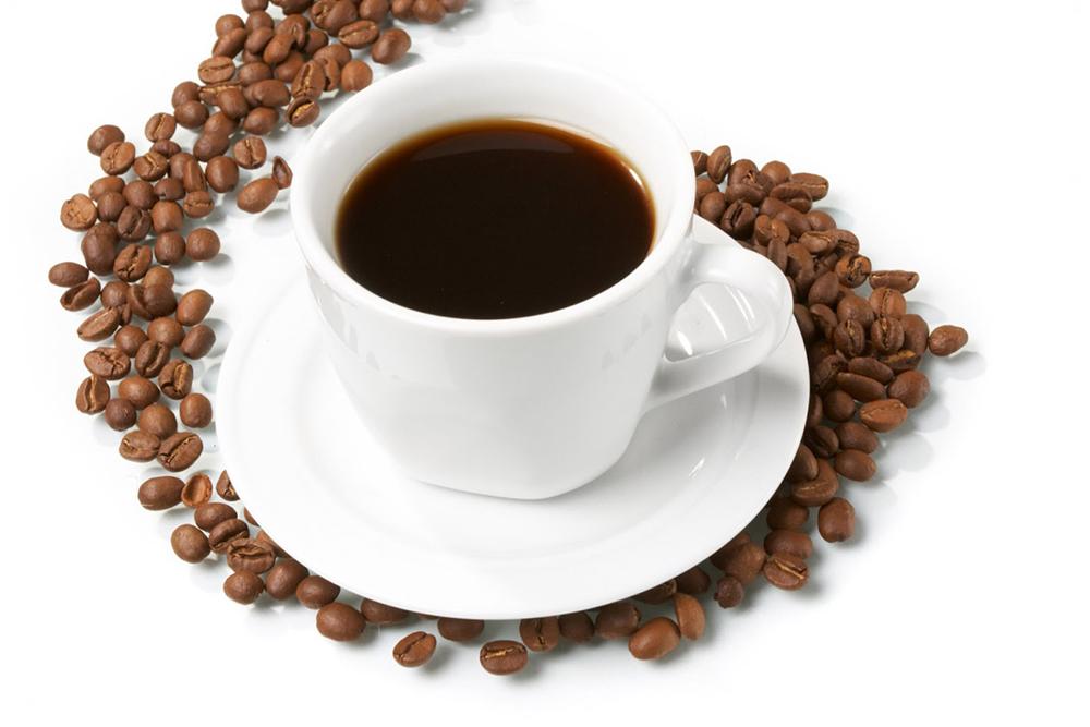 Kaffekopp med kaffe och kaffebönor vid sidan om